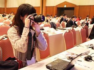 学生も報道席から有名新聞社と一緒に取材。一眼レフのカメラ撮影の技術も覚えます。